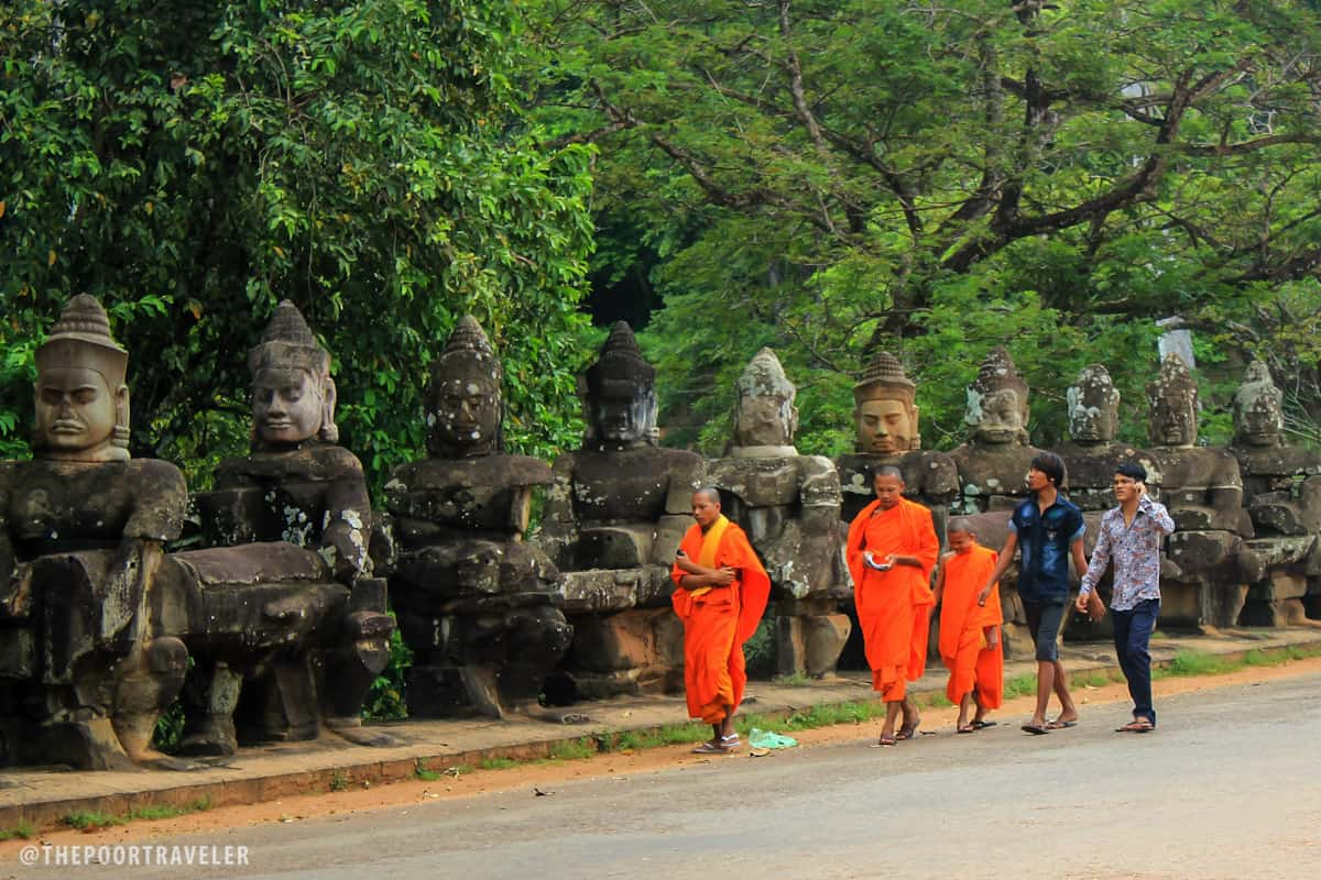 Buddhist Monks and some locals walking out of Angkor Thom through the South Gate