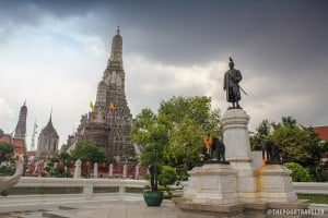 Statue of King Rama beside the prang of Wat Arun