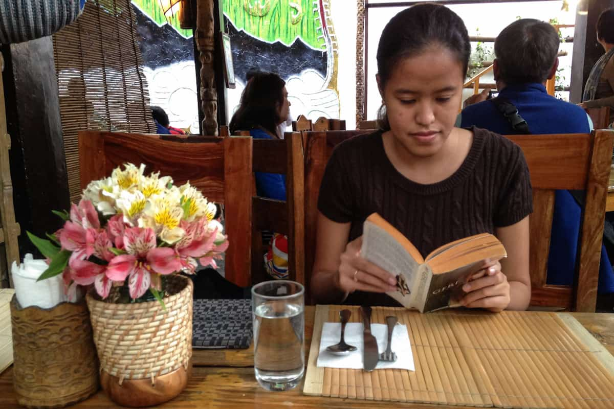 My friend Mica reading her time away while waiting for our meals