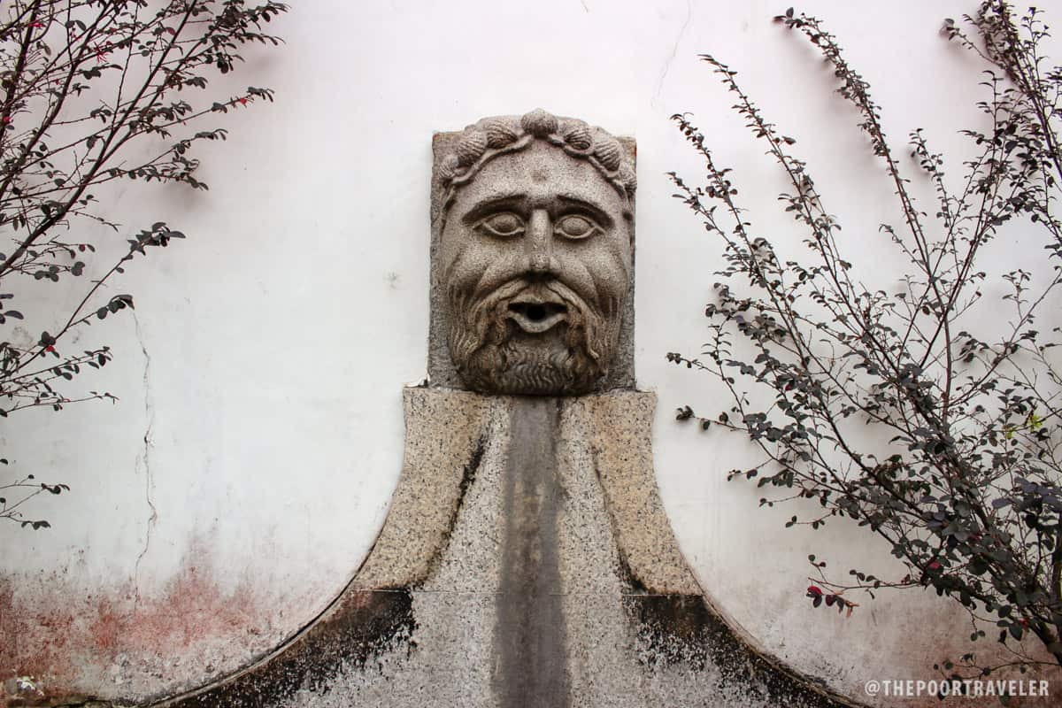 An old water fountain on the wall surrounding the garden