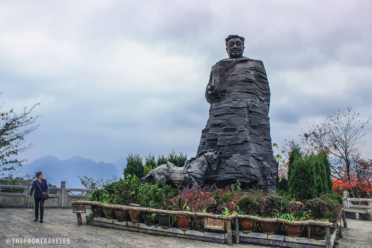 "Marshal He Long Park. Named after the legendary military leader, the park has a massive statue of him as its centerpiece. ""The statue looks like the peculiar peaks in Wulingyuan,"" reads the marker. By his side is his horse, symbolizing the glory of his military life."