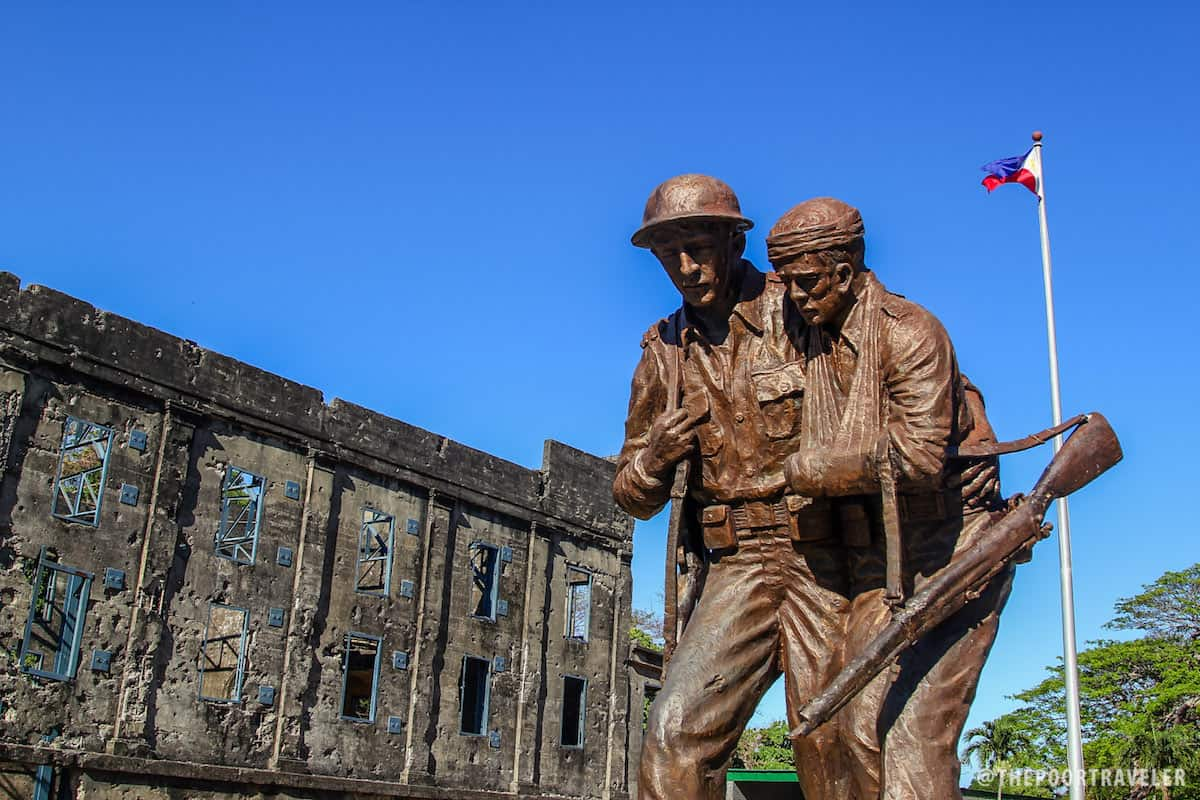 A statue of an American and a Filipino with the ruins of Cine Corregidor and the Philippine flag in the background.