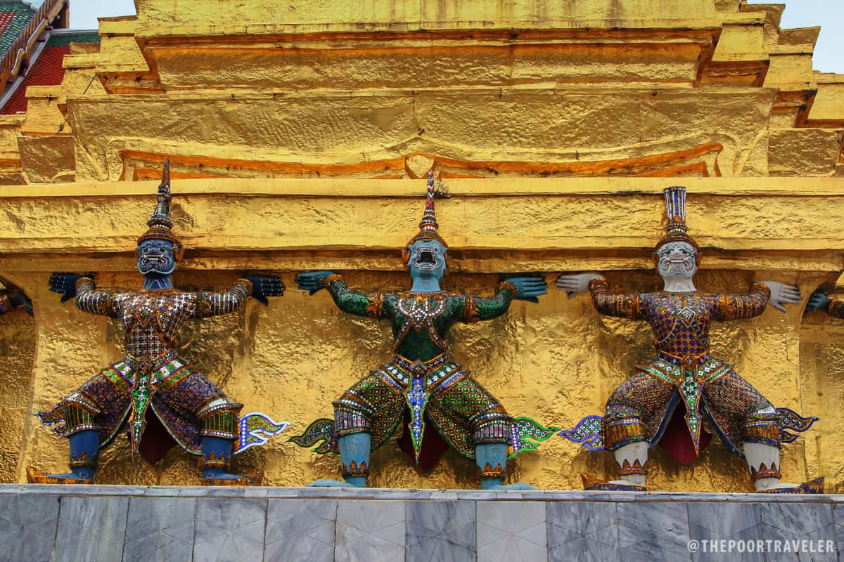 Statues of demons lifting the chedi at the Temple of the Emerald Buddha
