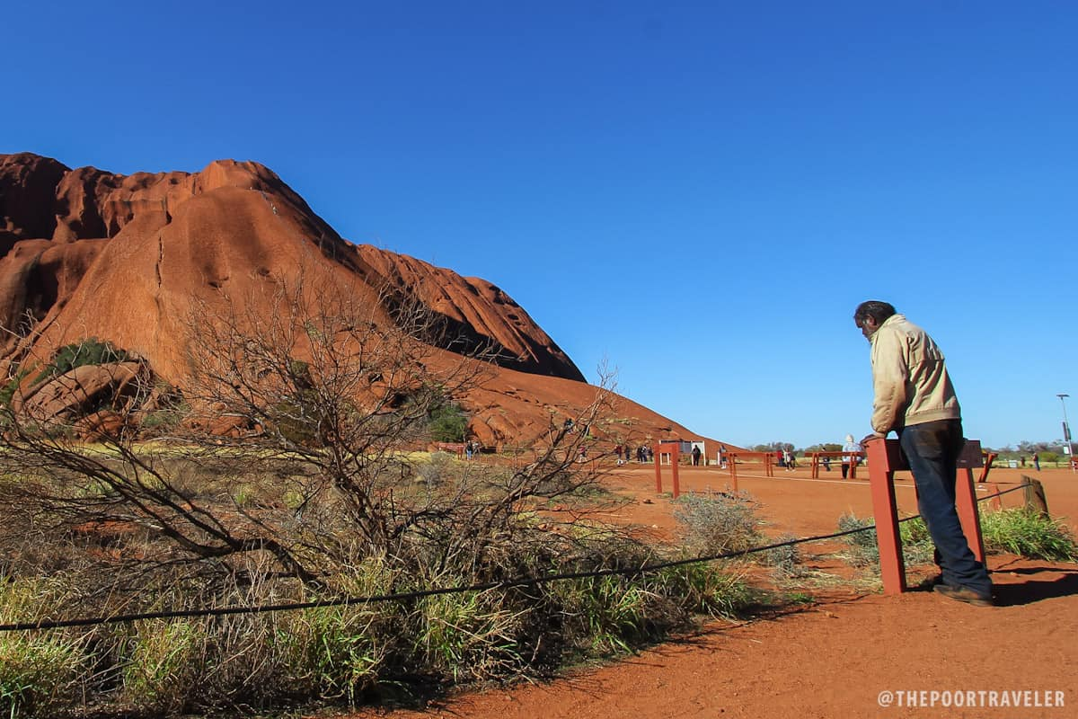 A local watching tourists climb Uluru