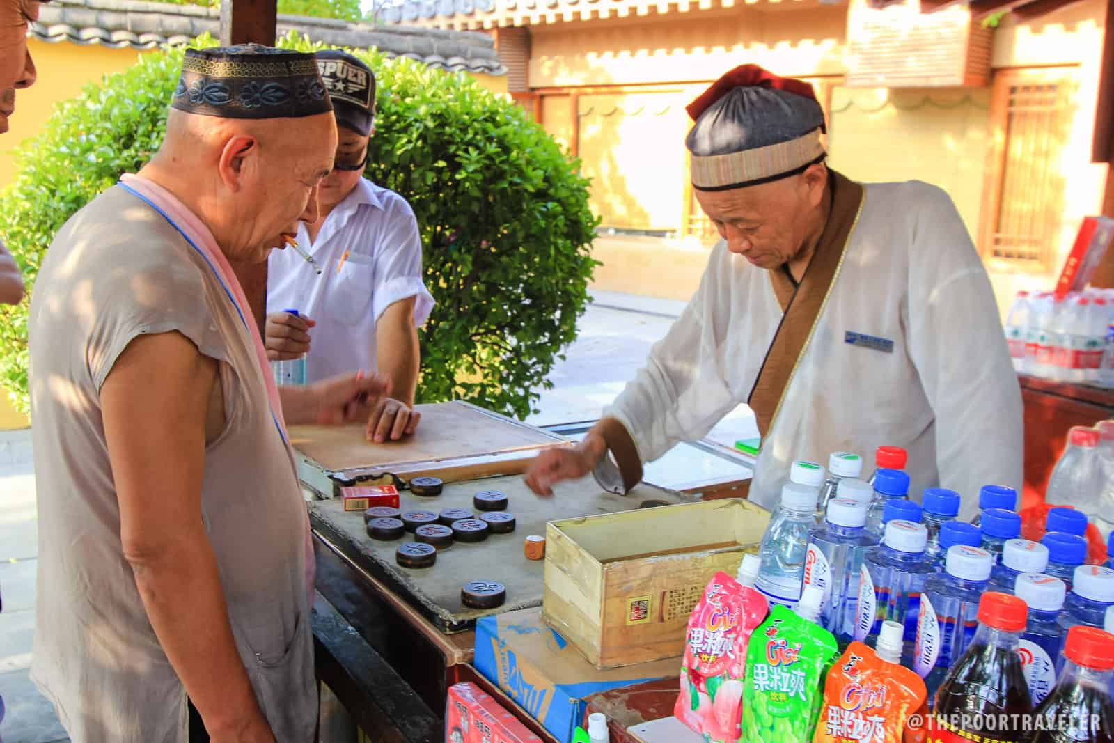 A stall vendor playing a board game.
